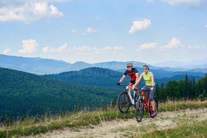 Молодые туристы, человек и женщина велосипедистов в велосипедах профессионального sportswear ехать вниз с травянистой дороги поля стоковая фотография rf