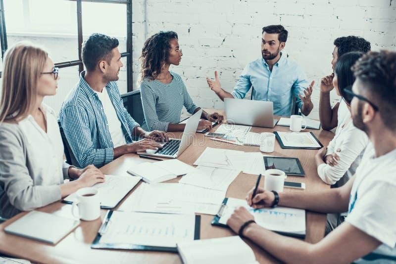 Молодые усмехаясь бизнесмены на встрече в офисе стоковая фотография