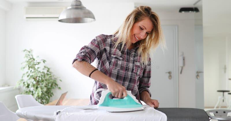 Молодые усмехаясь одежды женщины утюжа на утюжа доске стоковая фотография rf