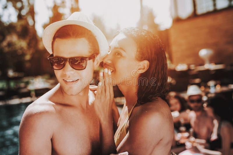 Молодые усмехаясь пары говоря на вечеринке у бассейна стоковые фотографии rf