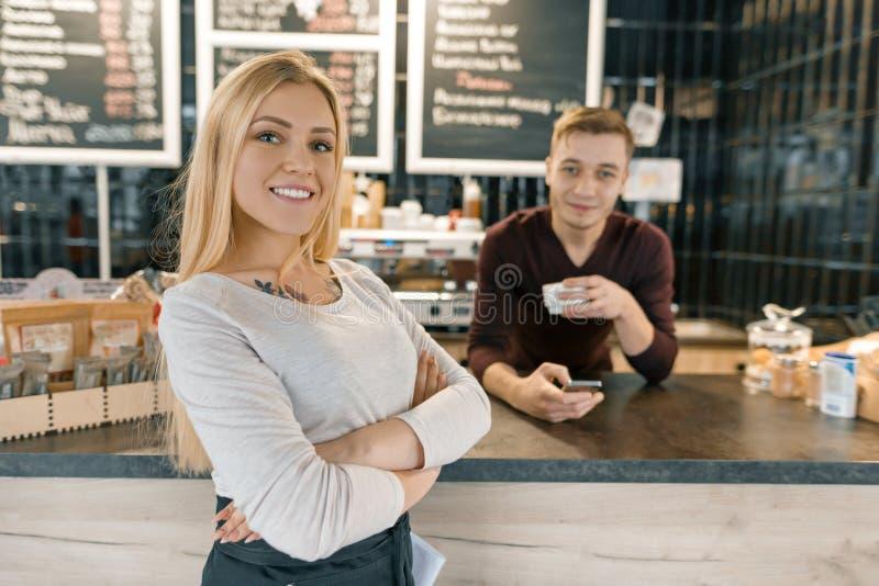Молодые усмехаясь пары работников, человека и женщины кофейни представляя около счетчика бара и машины кофе с чашкой свежего кофе стоковые фото