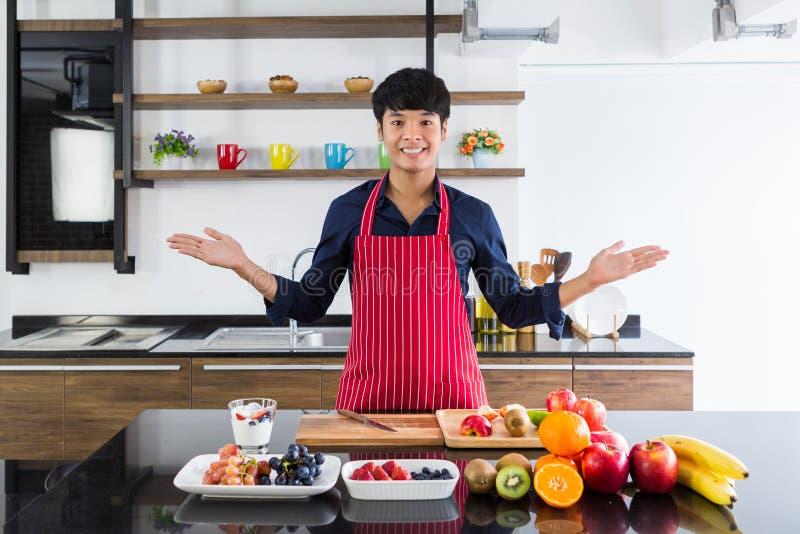 Молодые усмехаясь плоды азиатской руки показа человека присутствующие сортированные на черном деревянном столе стоковое фото