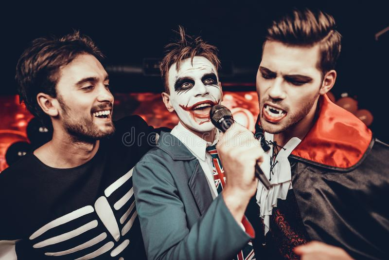 Молодые человеки в костюмах хеллоуина поя караоке стоковое изображение