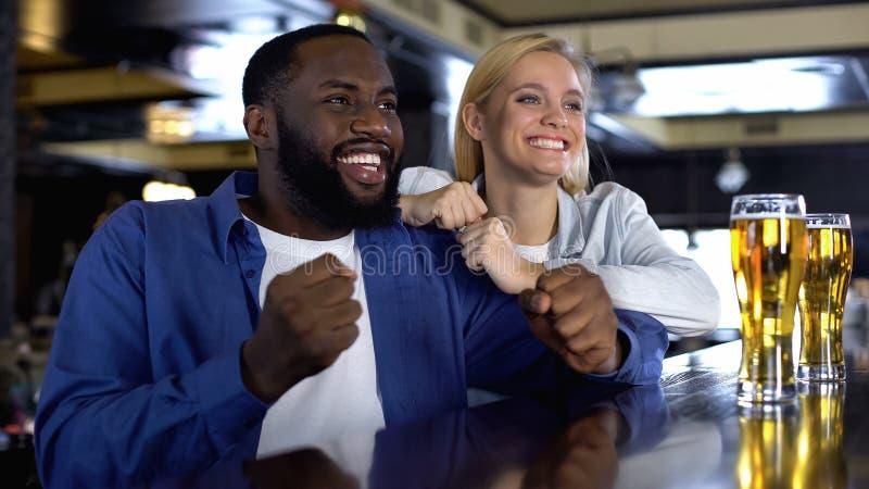 Молодые biracial пары укореняя любимую команду спорта в баре, наблюдая спичке онлайн стоковые фотографии rf