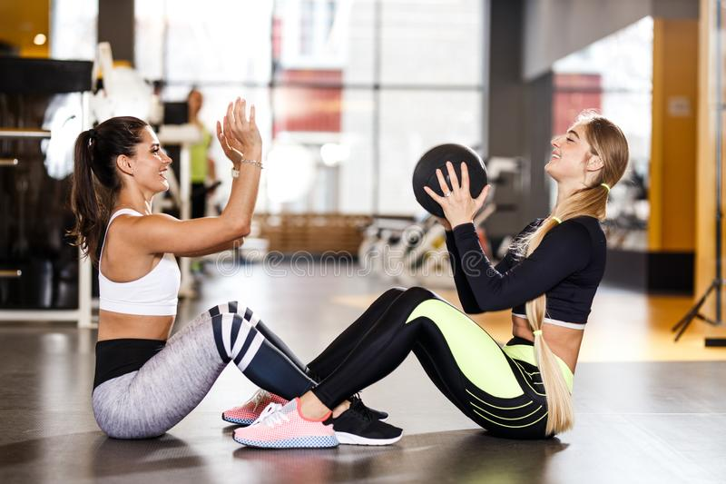 2 молодых атлетических девушки одетой в sportswear делают совместно тренировки спорта для прессы с шариком фитнеса в стоковые фотографии rf