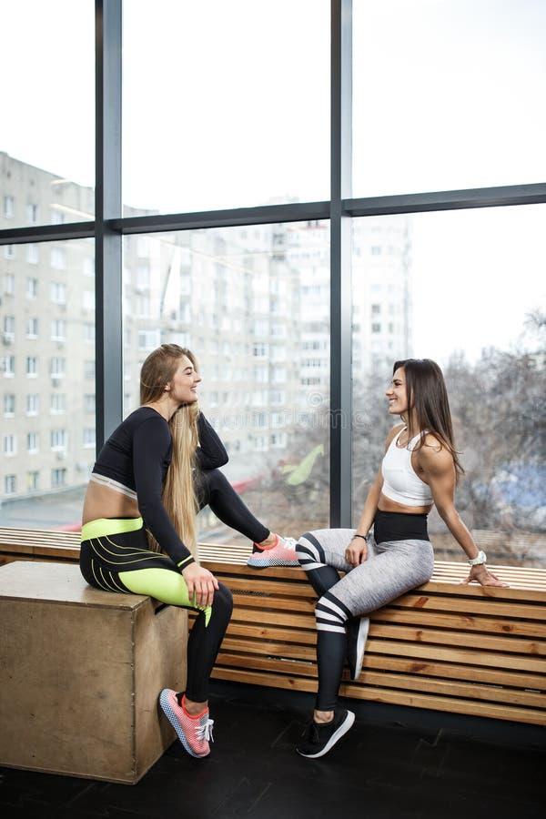 2 молодых атлетических девушки одетой в sportswear сидят на деревянном windowsill рядом с панорамными окнами в стоковые изображения rf