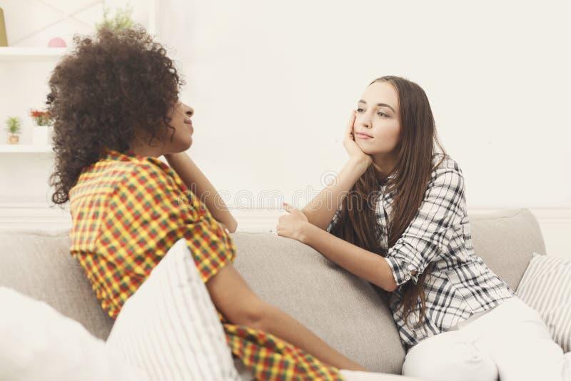 2 молодых женских друз с кофе беседуя стоковое изображение