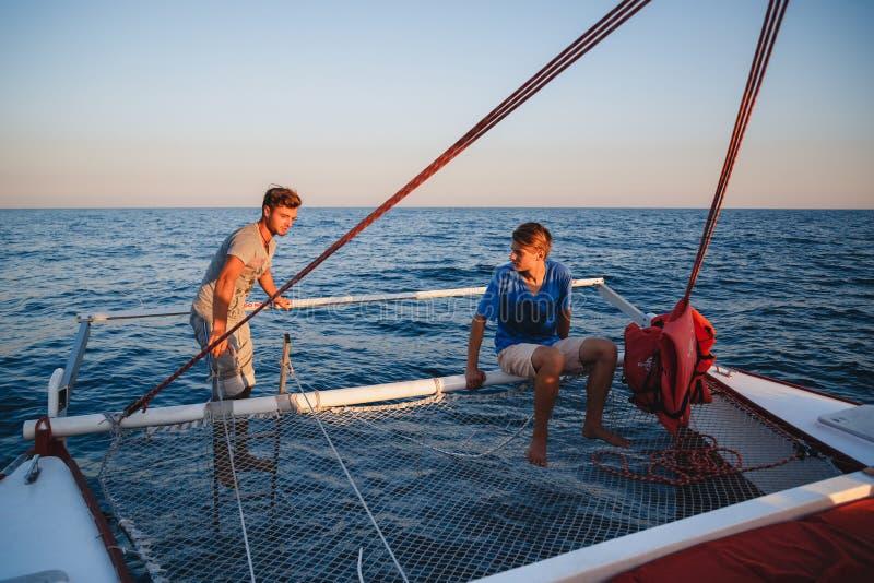 2 молодых красивых люд на в корме парусника подготавливая для нырять, капитана управляя яхтой в море на солнечном дне стоковые фото