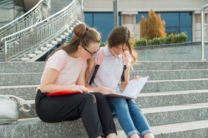 2 молодых красивых студента девушек с рюкзаками, книгами стоковая фотография