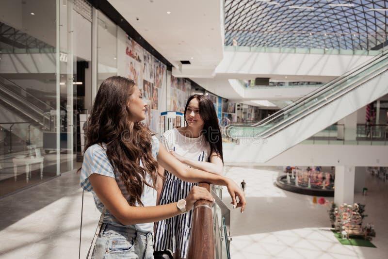 2 молодых милых тонких темн-с волосами девушки, стойка рядом друг с другом в современном торговом центре стоковое фото