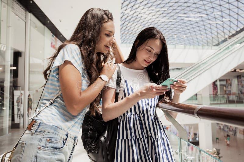 2 молодых милых тонких темн-с волосами девушки, стойка рядом друг с другом в современном торговом центре стоковая фотография