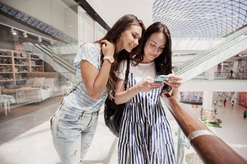 2 молодых милых тонких темн-с волосами девушки, стойка рядом друг с другом в современном торговом центре стоковое изображение