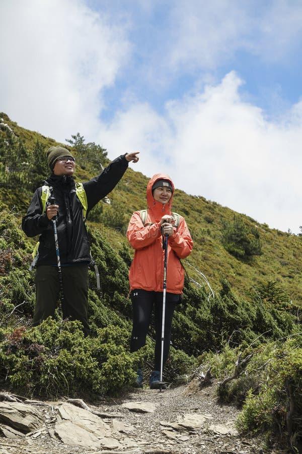 2 молодых пары нося внешние одежды стоят на холме, и мужские пункты похода на где-то для того чтобы позволить женскому hiker знаю стоковое изображение rf