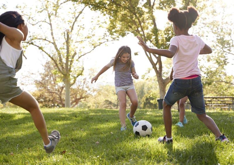4 молодых подруги пиная футбол совместно в парке стоковая фотография