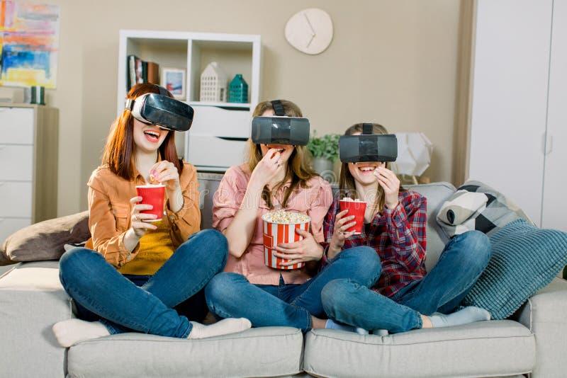 3 молодых привлекательных женщины нося изумленные взгляды зрения виртуальной реальности шлемофона VR наблюдая видео, сидя на софе стоковые фотографии rf
