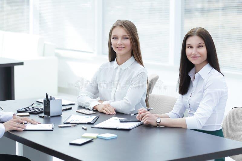 3 молодых работника сидя за столом стоковая фотография rf