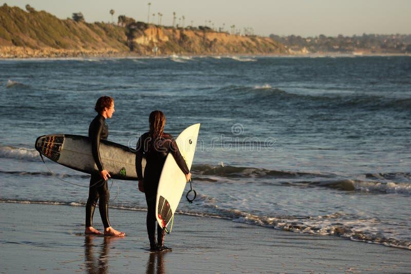 2 молодых серфера на ` s свами приставают к берегу в Encinitas Калифорнии стоковое изображение rf