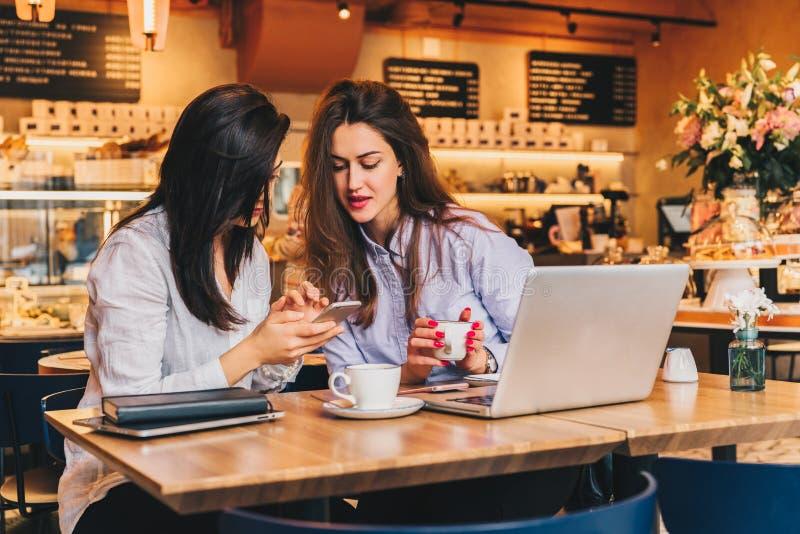 2 молодых счастливых женщины сидят в кафе на таблице перед компьтер-книжкой, используя smartphone и смеяться над стоковая фотография rf