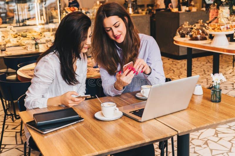 2 молодых счастливых женщины сидят в кафе на таблице перед компьтер-книжкой, используя smartphone и смеяться над стоковое фото rf