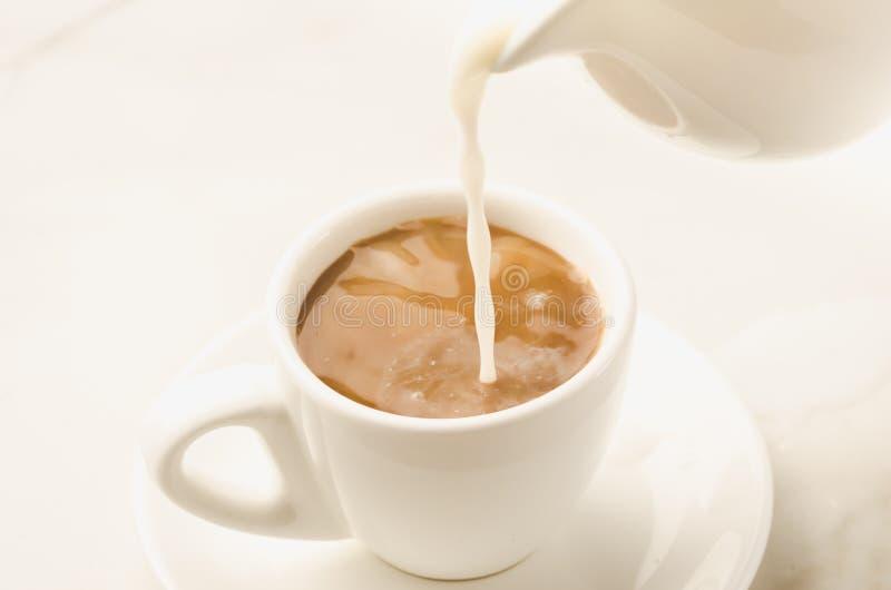 Молоко добавлено к кофейной чашке/молоку добавлено к кофейной чашке на whi стоковая фотография