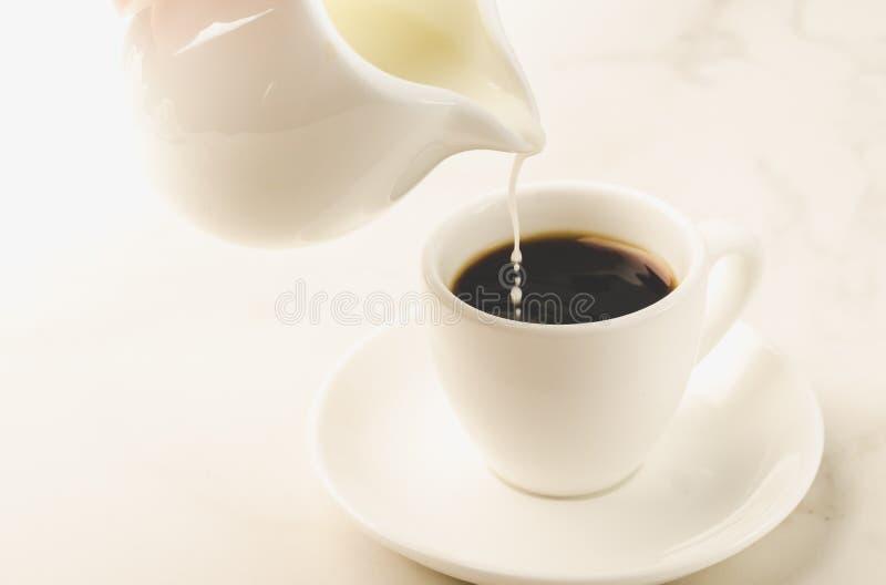 Молоко добавлено к кофе белая чашка/молоко добавлена к кофейной чашке дальше стоковое фото rf
