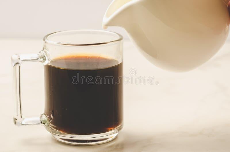 Молоко добавлено к стеклу кофе/молоку добавлено к стеклу кофе на w стоковые фото