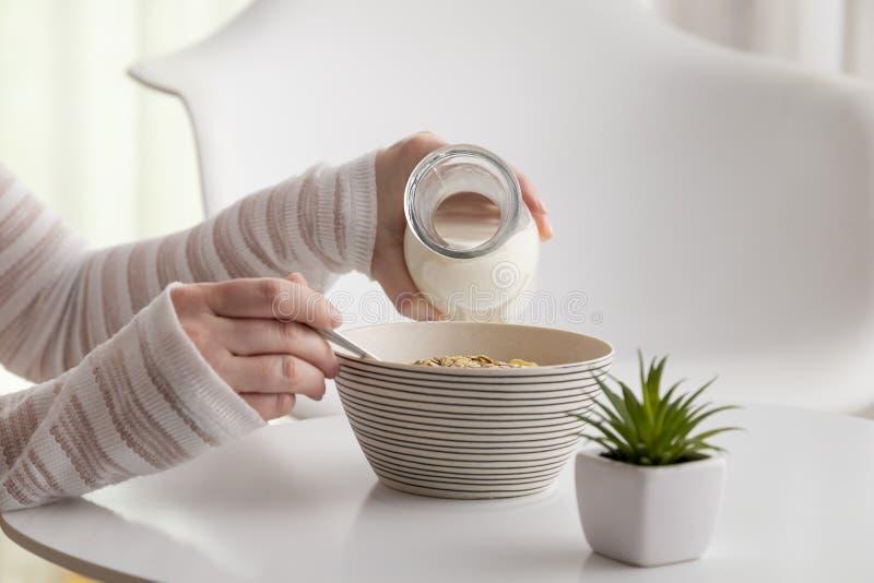 Молоко женщины лить в шар хлопьев стоковая фотография
