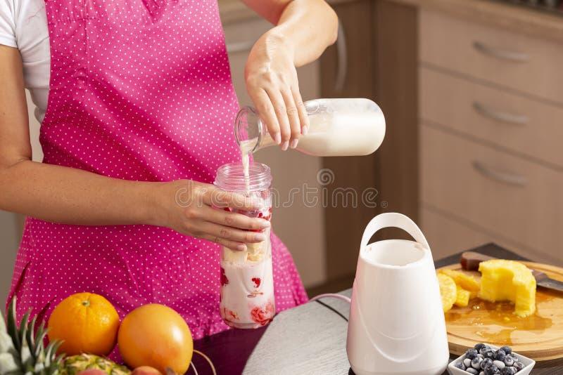 Молоко женщины лить в шар smoothie стоковые фотографии rf