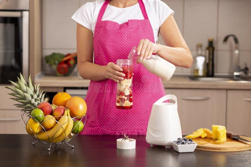 Молоко женщины лить в шар smoothie стоковое изображение rf