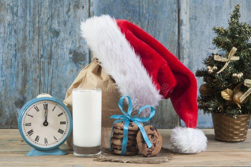 Молоко и печенья для шляпы Санта Клауса и Санта над деревянным bac стоковые фотографии rf
