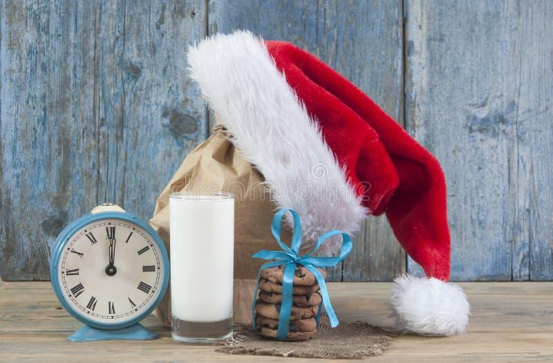 Молоко и печенья для шляпы Санта Клауса и Санта над деревянным bac стоковое фото rf