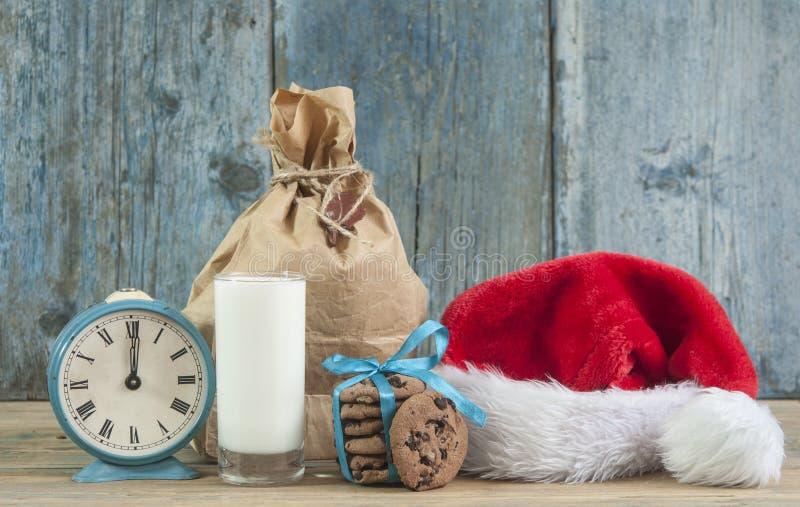 Молоко и печенья для шляпы Санта Клауса и Санта над деревянным bac стоковые фото