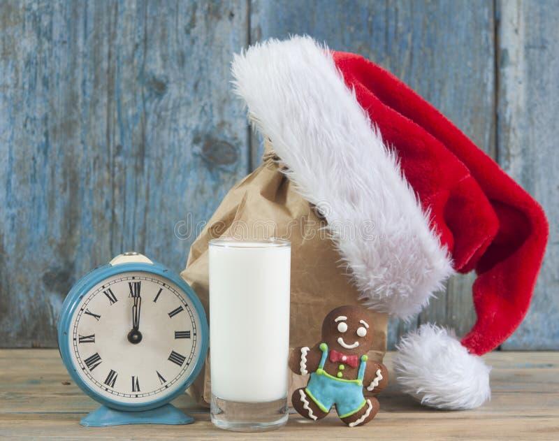Молоко и печенья для шляпы Санта Клауса и Санта над деревянным bac стоковые изображения rf