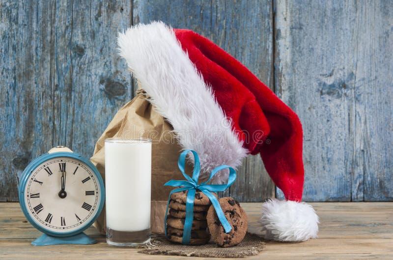 Молоко и печенья для шляпы Санта Клауса и Санта над деревянным bac стоковое изображение rf