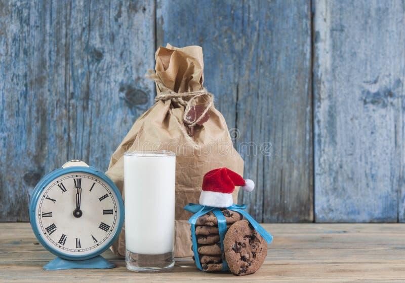 Молоко и печенья для шляпы Санта Клауса и Санта над деревянным bac стоковая фотография rf