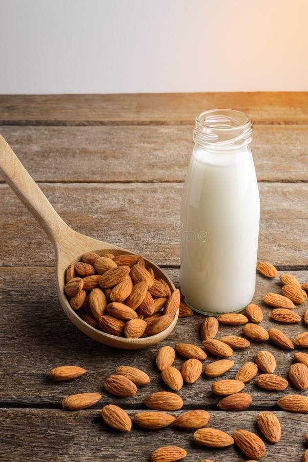 Молоко миндалины в бутылке с миндалинами льет от деревянной ложки стоковая фотография