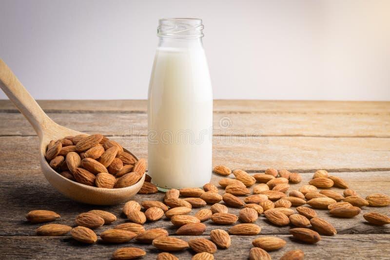 Молоко миндалины в бутылке с миндалинами льет от деревянной ложки стоковое фото
