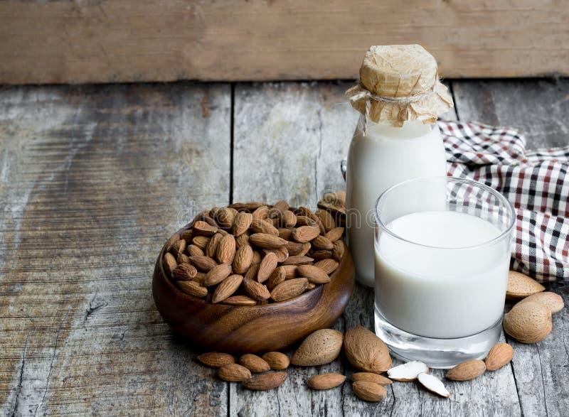Молоко миндалины в стеклянной бутылке на деревянном столе стоковое фото