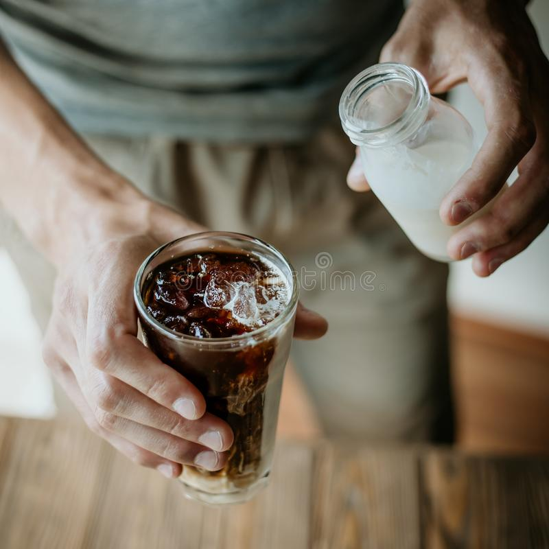 Молоко человека лить в замороженном кофе стоковая фотография