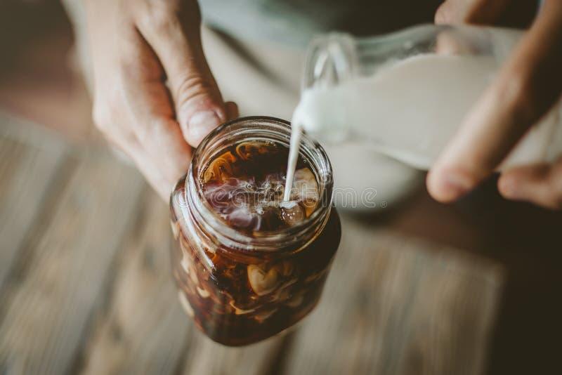 Молоко человека лить в замороженном кофе стоковое фото