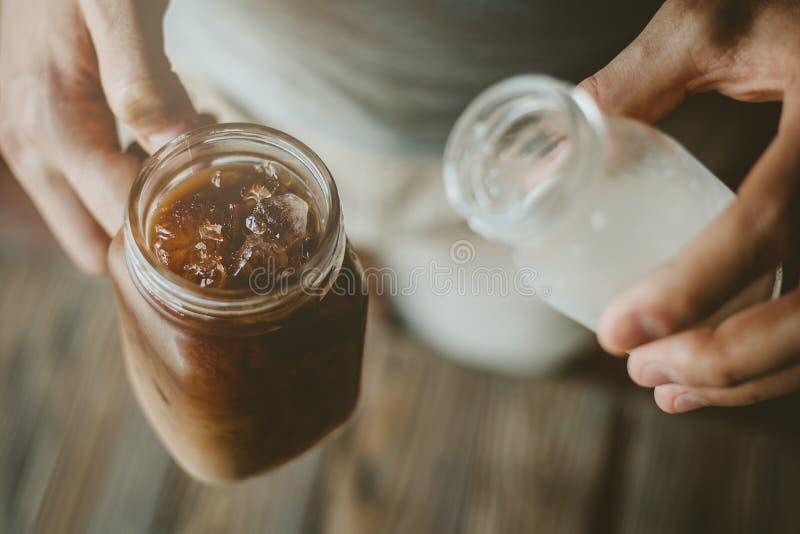 Молоко человека лить в замороженном кофе стоковое фото rf