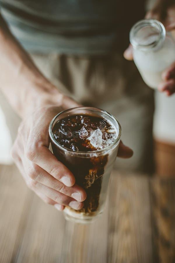 Молоко человека лить в замороженном кофе стоковая фотография rf
