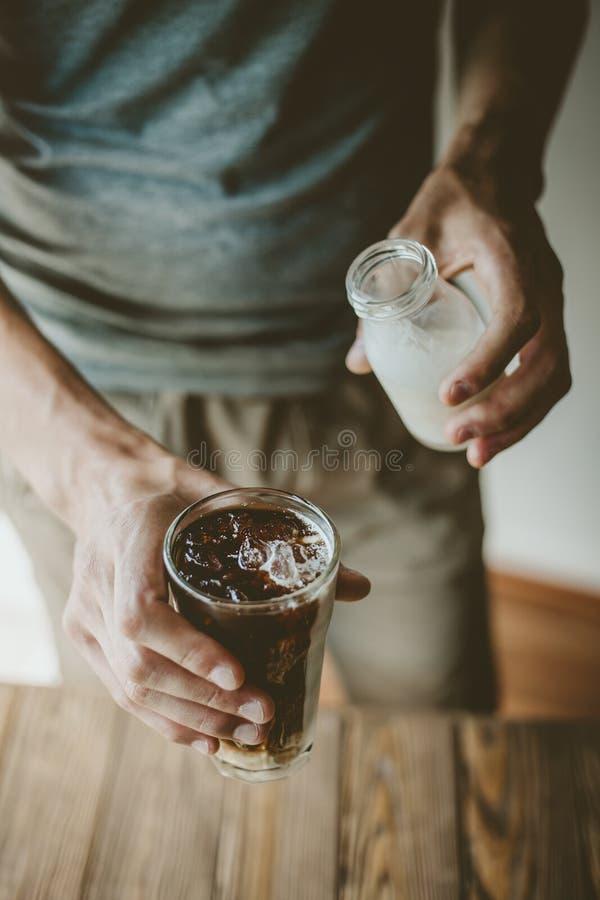 Молоко человека лить в замороженном кофе стоковые фотографии rf