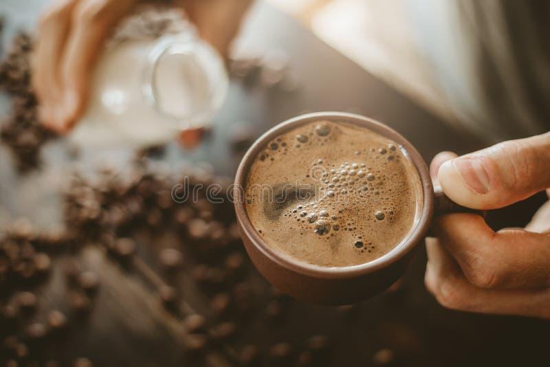 Молоко человека лить в испаренном кофе стоковая фотография
