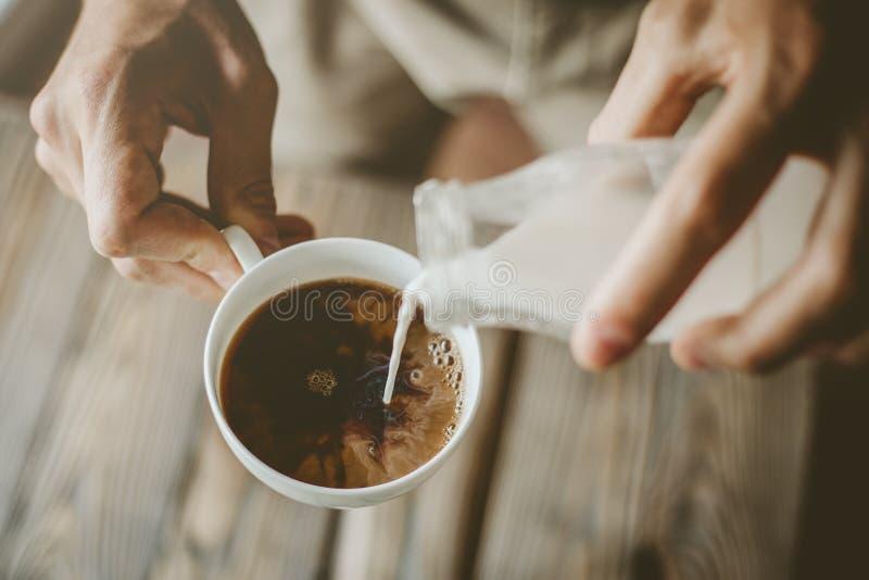 Молоко человека лить в испаренном кофе стоковые изображения