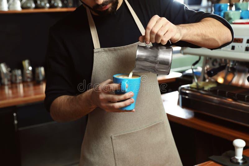 Молоко Barista лить в чашку кофе в магазине стоковые изображения