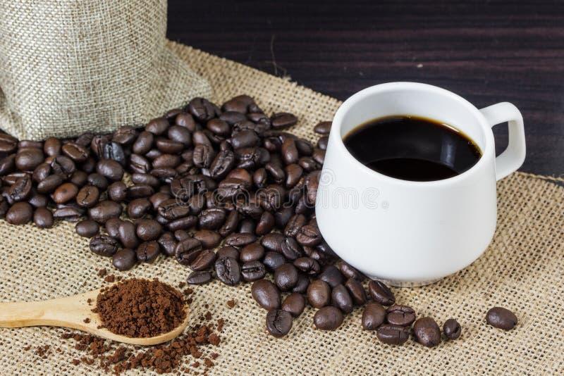Молотилка кофе в деревянной ложке на дерюге с предпосылкой кофейных зерен скопируйте космос стоковые изображения rf