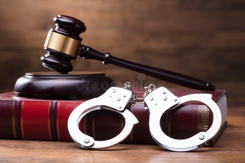 Молоток и наручники на книге по праву стоковая фотография