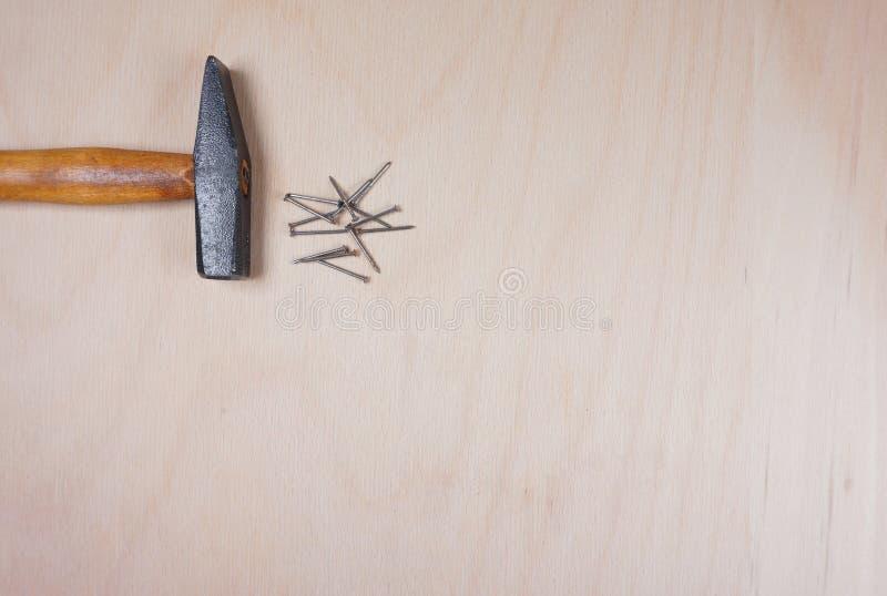 Молоток и ногти на деревянной предпосылке с космосом для вашего собственного текста для приглашения для мастерской etc стоковые фотографии rf