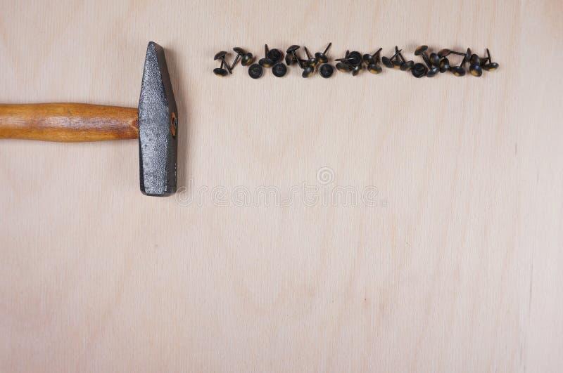 Молоток и ногти на деревянной предпосылке с космосом для вашего собственного текста для приглашения для мастерской, fathersday et стоковая фотография